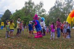 村庄和竞争的假日天有设计卡通者和儿童的游乐场的在秋天的公园 免版税库存照片