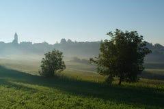 村庄和草甸在有薄雾的早晨 免版税库存照片
