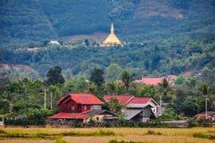 村庄和金黄stupa在Luang Nam Tha,老挝 免版税库存图片