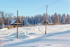 村庄在一个积雪的森林附近的冬天 库存图片