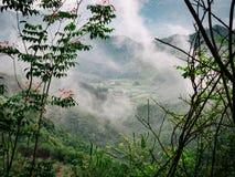 村庄在山附近的被看见的thorugh云彩 免版税库存照片