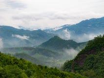 村庄在山附近的被看见的thorugh云彩 库存图片