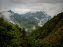 村庄在山附近的被看见的thorugh云彩 库存照片