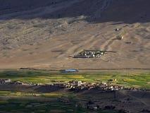 村庄在山:在棕色小山的基地有大麦的绿色领域,在农舍的倾斜和 免版税库存图片