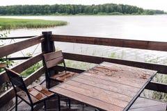 村庄在河附近的森林里有大木大阳台的 水的议院在湖,一家美丽的银行 理想的地方为 免版税库存照片