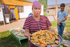 """村庄妇女烹调了全国吉尔吉斯面包""""borsok"""" 免版税图库摄影"""