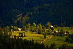 村庄安置在山,森林的上流 免版税库存照片