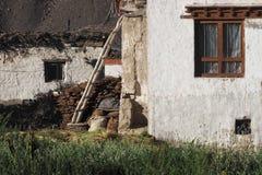 村庄庭院:在房子逐个透视白色黏土墙壁,一个木楼梯倾斜了对墙壁,上流 免版税库存图片