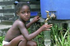 村庄生活,从接雨水的桶的流失雨水 免版税库存图片