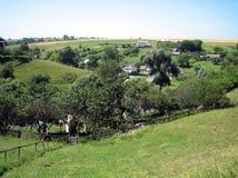 村庄的全景小山的与庭院,果树园,有豪华的绿叶的在一清楚的好日子 免版税库存照片