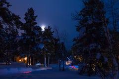 村庄的圣诞节照明设备在冬天森林和月亮里 免版税库存图片