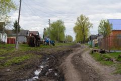 村庄街道照片有拖拉机和土路的 库存照片