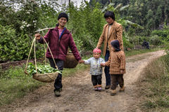 村民在中国,有孩子的妇女,是在乡下公路 库存照片