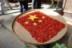 村民投入胡椒,并且菊花到中国五里担任主角红旗,多孔黏土rgb 免版税库存照片