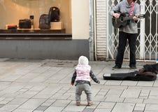 杜塞尔多夫,德国- 2017年2月13日:一个未认出的孩子听Bolker的Strasse一位街道音乐家 免版税库存图片