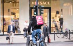 杜塞尔多夫,德国- 2017年5月03日:一个未认出的Foodora交付骑自行车的人横渡Koenigsallee 库存照片