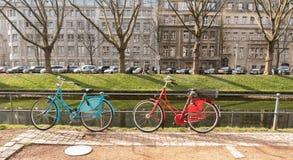 杜塞尔多夫,德国- 2017年3月13日:两五颜六色的bycicles在扶手栏杆倾斜在Koenigsallee并且反射春天 库存图片