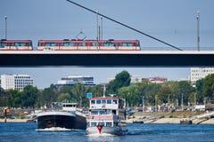 杜塞尔多夫,德国- 2016年9月14日:两艘船通过有电车轨道的莱茵河桥梁 库存图片