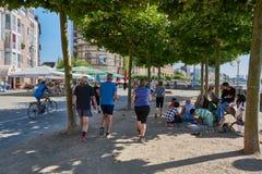 杜塞尔多夫,德国- 2016年8月17日:未认出的慢跑者通过采取休息的一个小组未认出的人民 库存图片
