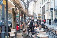 杜塞尔多夫,德国- 2017年3月12日:未认出的顾客沿Koenigsallee漫步并且通过一个风景咖啡馆与 库存图片