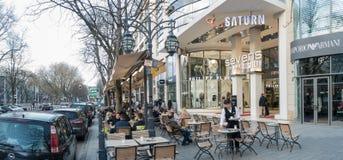 杜塞尔多夫,德国- 2017年3月12日:未认出的顾客沿Koenigsallee漫步并且通过一个风景咖啡馆与 图库摄影