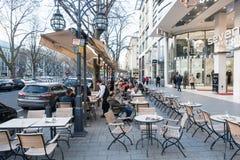 杜塞尔多夫,德国- 2017年3月12日:未认出的顾客沿Koenigsallee漫步并且通过一个风景咖啡馆与 库存照片