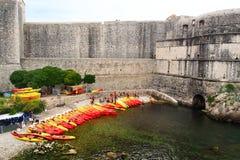杜布罗夫尼克,克罗地亚- 2017年6月02日:全部红色和黄色kayacs在岸拉扯了在杜布罗夫尼克老堡垒的墙壁附近 免版税库存照片