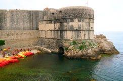 杜布罗夫尼克,克罗地亚- 2017年6月02日:全部红色和黄色kayacs在岸拉扯了在杜布罗夫尼克老堡垒的墙壁附近 库存图片