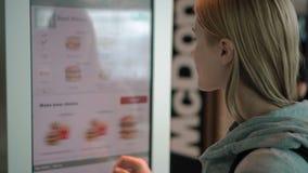 杜拜机场,大约2017年3月的阿拉伯联合酋长国:妇女预定的食物通过在麦克唐纳` s的自助机器 股票视频