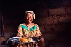 杜阿拉喀麦隆- 06威严2018年:老非洲夫人特写镜头在她的有看在照相机的传统礼服的农村家庭厨房里 免版税库存图片