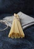 束与亚麻布餐巾的未加工的意大利意粉面团在黑暗的石桌上 库存图片