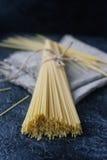 束与亚麻布餐巾的未加工的意大利意粉面团在黑暗的石桌上 免版税库存照片