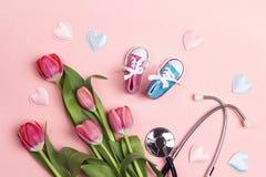 束与听诊器和童鞋的郁金香在桃红色背景 免版税库存照片