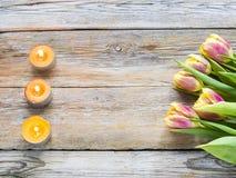 束与蜡烛的桃红色郁金香在土气木背景 免版税图库摄影