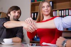 结束在办公室内部的一个成交的商人加入的手 免版税库存照片