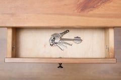 束在圆环的门钥匙在开放抽屉 库存图片