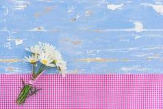束在土气浅兰的木头的延命菊雏菊与桃红色检查了纺织品边界生日或母亲节卡片 免版税库存图片