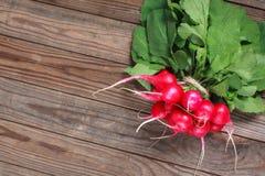 束在木桌上的新鲜的萝卜 库存照片