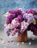 束在木桶匠葡萄酒水罐的淡紫色花 蓝色背景拷贝空间 库存照片