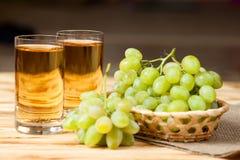 束在柳条筐的新鲜的成熟绿色葡萄在麻袋布片断和两块玻璃用在木织地不很细ba的葡萄汁 图库摄影
