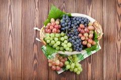 束在篮子的红色,紫色和白葡萄 免版税库存照片