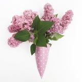 束在纸锥体的淡紫色花在从上面白色背景,平的位置 免版税库存图片