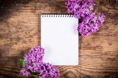 束在老桌上的丁香与垂直的空白的笔记本 免版税库存图片