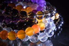 束在黑背景-光玉髓,紫晶,石英的次贵重的宝石镯子 免版税图库摄影