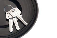 束在黑茶碟的三把钥匙 库存照片