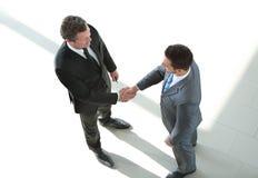 结束成交和握手的商人在办公室 库存照片