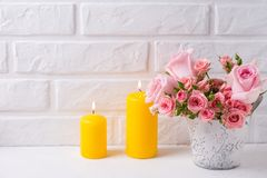 束新鲜的桃红色玫瑰在罐和两个黄色蜡烛开花 免版税图库摄影