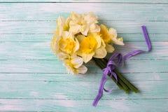 束新鲜的黄色水仙在被绘的绿松石开花 免版税库存照片