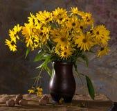 束明亮的黄色花(黄金菊)在棕色花瓶和wal 免版税库存图片