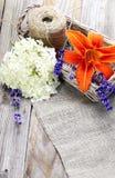 束淡紫色花和百合在篮子在一个老木选项 免版税库存图片